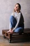 Muchacha en el suéter que se sienta en una cubierta Fondo gris Fotografía de archivo