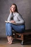 Muchacha en el suéter que sostiene el libro y que se sienta en una cubierta Fondo gris Fotos de archivo
