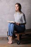 Muchacha en el suéter que sostiene un libro Fondo gris Imagen de archivo