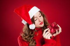 Muchacha en el suéter rojo que lleva a cabo el regalo de Navidad que lleva a Santa Clau Imágenes de archivo libres de regalías