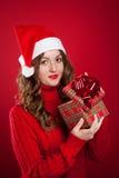 Muchacha en el suéter rojo que lleva a cabo el regalo de Navidad que lleva a Santa Clau Fotos de archivo
