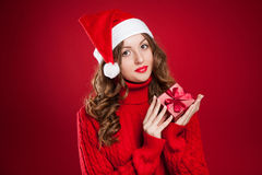 Muchacha en el suéter rojo que lleva a cabo el regalo de Navidad que lleva a Santa Clau Imagen de archivo libre de regalías