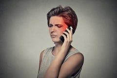 Muchacha en el teléfono con dolor de cabeza Concepto móvil celular de la radiación Fotografía de archivo