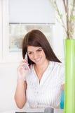 Muchacha en el teléfono en casa Imagenes de archivo
