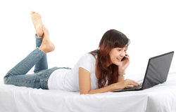 Muchacha en el teléfono en cama con la computadora portátil Imagen de archivo