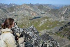 Muchacha en el top de un acantilado, mirando sobre el valle y el lago Fotografía de archivo libre de regalías