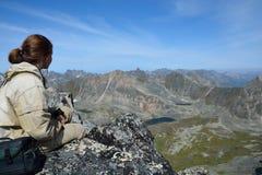 Muchacha en el top de un acantilado, mirando sobre el valle y el lago Foto de archivo