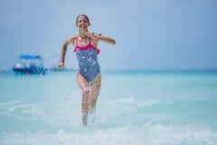 Muchacha en el traje de baño que funciona con y que se divierte en la playa tropical Imagen de archivo