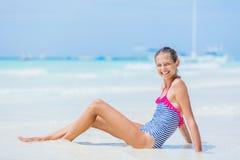 Muchacha en el traje de baño que sienta y que se divierte en la playa tropical Fotos de archivo libres de regalías