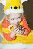 Muchacha en el traje de la Navidad de la ardilla con el árbol de navidad del pinecone Fotografía de archivo libre de regalías