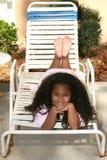 Muchacha en el traje de la piscina que pone en silla de salón Imagen de archivo