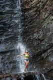 Muchacha en el traje de natación que se coloca debajo de la cascada Imágenes de archivo libres de regalías