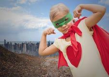 Muchacha en el traje del super héroe que dobla sus brazos contra paisaje urbano Fotografía de archivo libre de regalías