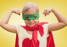 Muchacha en el traje del super héroe que muestra los puños contra fondo amarillo Imagen de archivo libre de regalías
