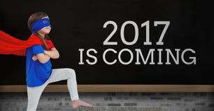 Muchacha en el traje del super héroe que se coloca cerca de un tablero con 2017 citas del Año Nuevo Imágenes de archivo libres de regalías