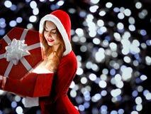 Muchacha en el traje rojo que sostiene un regalo por el Año Nuevo 2018,2019 Imagen de archivo