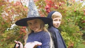 Muchacha en el traje y el muchacho-vampiro de la bruja que presentan para la cámara, celebración de Halloween metrajes