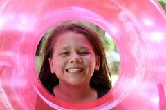 Muchacha en el tubo interno rosado que se divierte Imagen de archivo libre de regalías