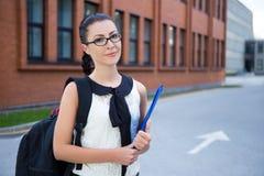 Muchacha en el uniforme escolar que se coloca en campus Imagen de archivo libre de regalías