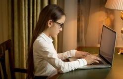 Muchacha en el uniforme escolar que se sienta detrás de la tabla y que usa el ordenador portátil en Fotos de archivo