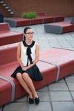 Muchacha en el uniforme escolar que se sienta en banco Foto de archivo