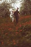 Muchacha en el uniforme que lleva un caballo a través del campo de flores foto de archivo libre de regalías