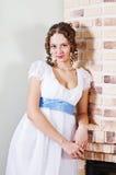 Muchacha en el vestido antiguo que coloca la chimenea cercana Fotografía de archivo libre de regalías