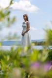 Muchacha en el vestido blanco en el lago Foto de archivo