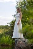 Muchacha en el vestido blanco en el lago en el verde contra el cielo Foto de archivo