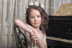 Muchacha en el vestido blanco en el piano Imagen de archivo libre de regalías