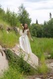 Muchacha en el vestido blanco, muro de cemento Fotos de archivo