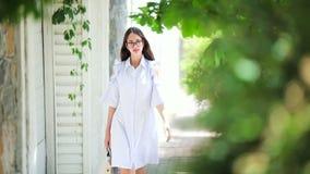 Muchacha en el vestido blanco que camina en la calle metrajes