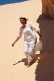 Muchacha en el vestido blanco que corre cerca de la montaña Fotografía de archivo libre de regalías