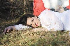 Muchacha en el vestido blanco que miente en la hierba Fotos de archivo libres de regalías