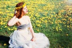 Muchacha en el vestido blanco que se sienta en un claro de dientes de león fotos de archivo