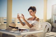 Muchacha en el vestido blanco el vacaciones Se sienta por la tabla Resto, viaje, vacaciones túnez Fotos de archivo libres de regalías