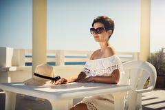 Muchacha en el vestido blanco el vacaciones Se sienta por la tabla Resto, viaje, vacaciones túnez Fotografía de archivo