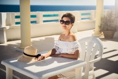 Muchacha en el vestido blanco el vacaciones Se sienta por la tabla Resto, viaje, vacaciones túnez Imágenes de archivo libres de regalías