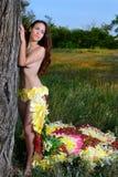 Muchacha en el vestido del firebird de flores cerca del árbol Fotografía de archivo libre de regalías