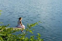 Muchacha en el vestido del verano que se sienta en la cubierta sobre el agua Foto de archivo libre de regalías