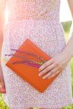 Muchacha en el vestido del verano que sostiene un libro Fotos de archivo libres de regalías