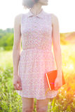 Muchacha en el vestido del verano que sostiene un libro Imagen de archivo libre de regalías