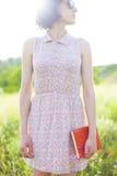 Muchacha en el vestido del verano que sostiene un libro Fotografía de archivo libre de regalías