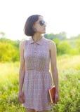 Muchacha en el vestido del verano que sostiene un libro Foto de archivo libre de regalías