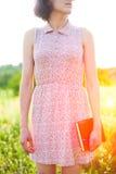 Muchacha en el vestido del verano que sostiene un libro Imagen de archivo