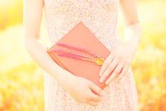 Muchacha en el vestido del verano que sostiene un libro Imágenes de archivo libres de regalías