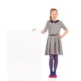 Muchacha en el vestido gris que presenta con un cartel en blanco Foto de archivo libre de regalías