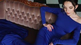 Muchacha en el vestido largo azul que miente en un sofá viejo almacen de metraje de vídeo
