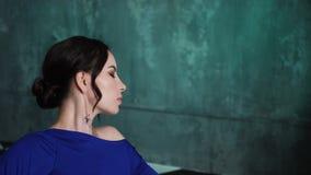 Muchacha en el vestido largo azul que miente en un sof? viejo almacen de video