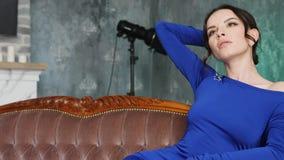 Muchacha en el vestido largo azul que miente en un sof? viejo metrajes